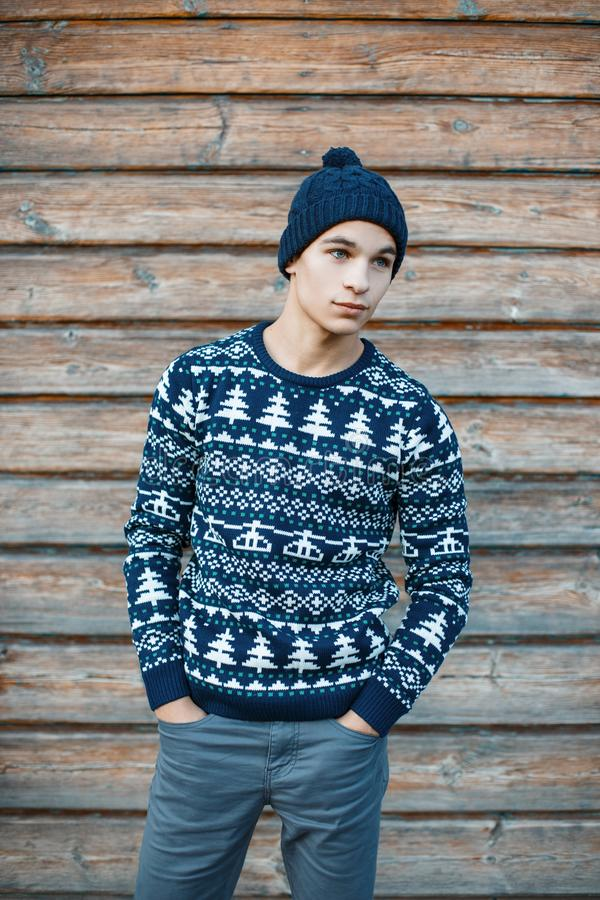 Fashionable handsome young man in stylish jeans in a knitted hat in a vintage festive blue sweater with a white pattern stock photo