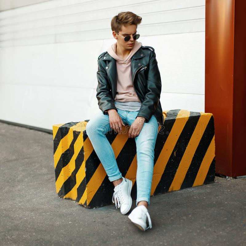 Fashionable handsome young man in stylish modern brand clothes. Sits on a black-and-yellow shoulder royalty free stock photo