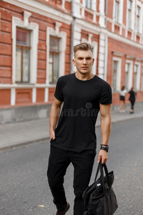 Fashionable handsome young stylish model man with hairstyle. In black stylish clothes with a black bag walks on the street in the city stock images
