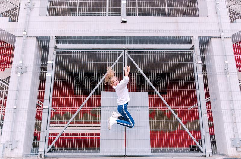Fashionable and happy teen girl jumping on the background of the building and the lattice. Photo of fashionable and happy teen girl jumping on the background of stock images