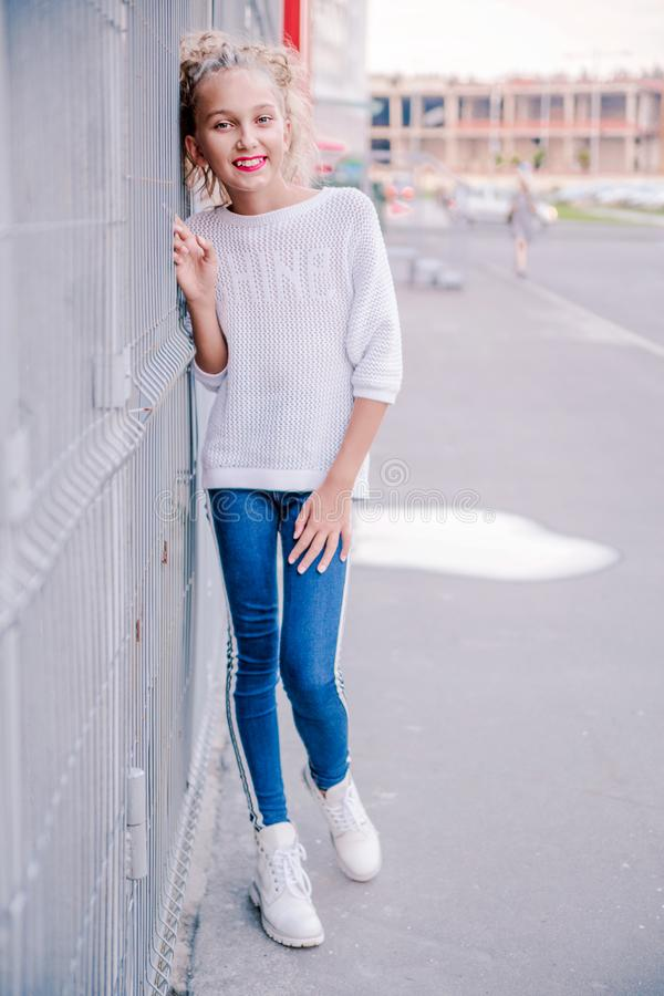Fashionable and happy teen girl posing against a background of a building and lattice royalty free stock photos