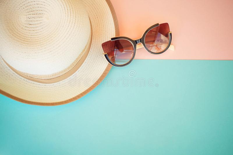 Fashionable hat and sunglasses on a colored background. stock photo