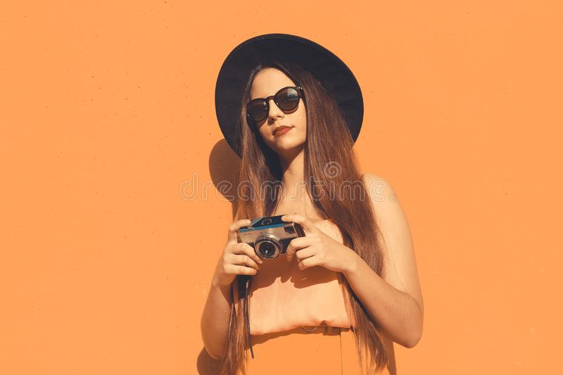 A fashionable  hipster girl with a vintage photo camera royalty free stock photos