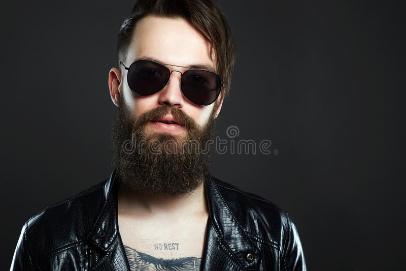 Fashionable hipster man with tattoo and sunglasses. Brutal bearded boy in trendy glasses stock images