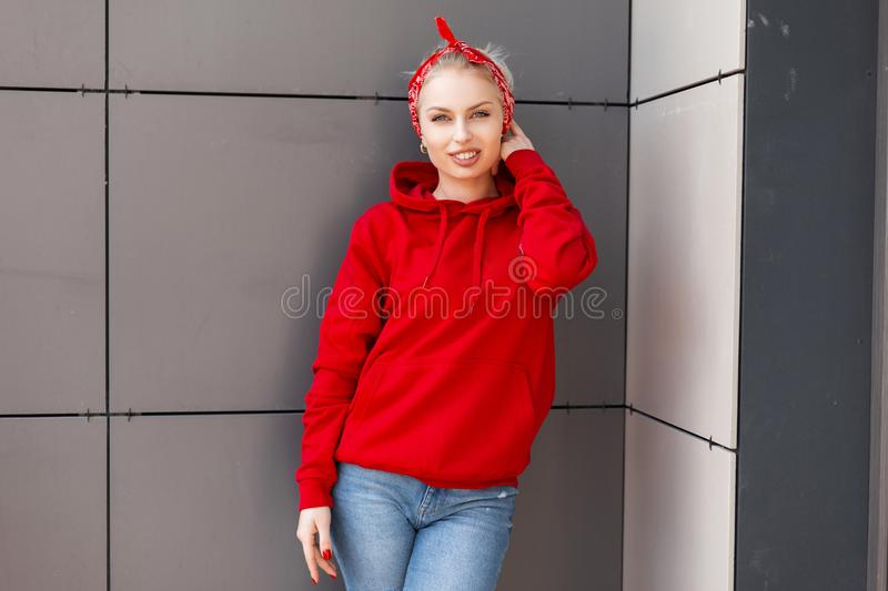 Fashionable joyful young woman with a cute smile in modern fashionable clothes with a red bandana is standing. Near a gray vintage building on a warm summer day royalty free stock photo