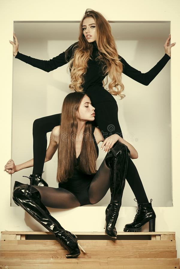 Fashionable ladies with make up and skinny legs posing, white background. Girls with long hair on mysterious faces. Posing in black clothes. Fashion and beauty royalty free stock photos