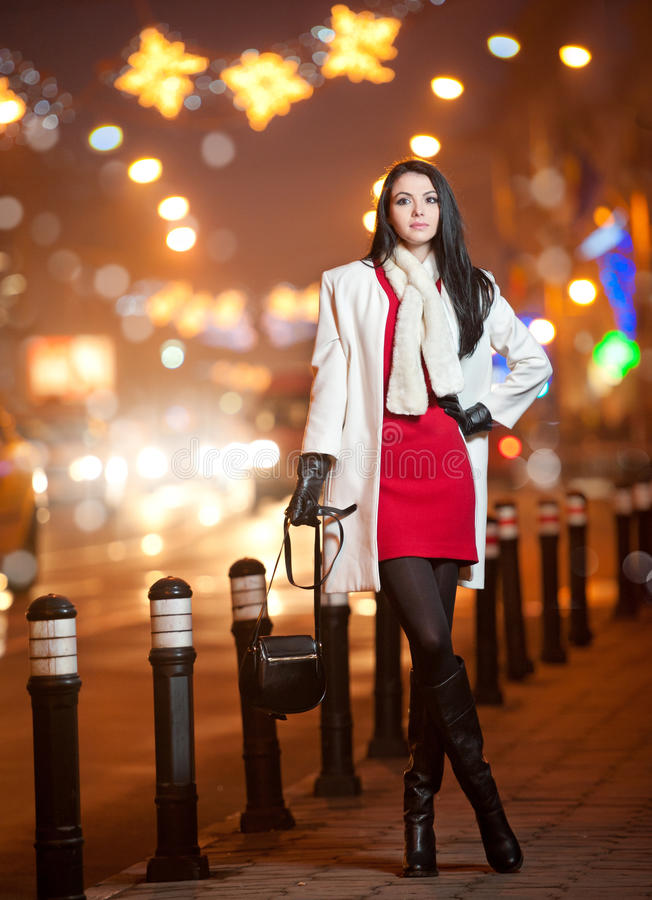 Fashionable lady wearing red dress and white coat outdoor in urban scenery with city lights in background. Full length portrait. Of young beautiful elegant stock photos