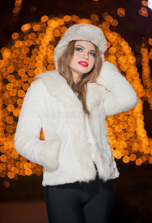 Fashionable lady wearing white fur cap and coat outdoor with bright Xmas lights in background. Portrait of young beautiful woman. In winter style. Bright stock photo