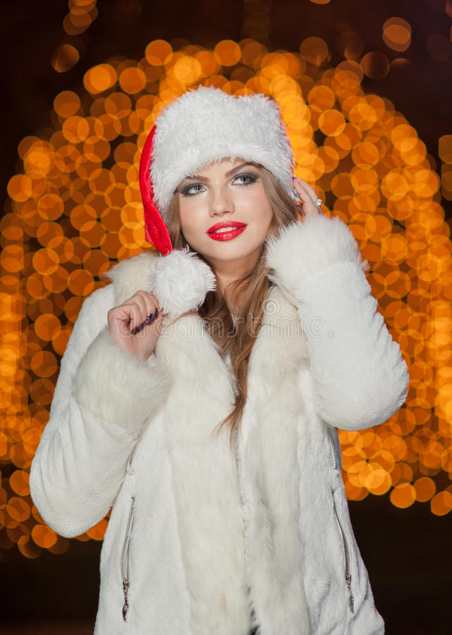 Fashionable lady wearing Xmas hat and white fur coat outdoor. Portrait of young beautiful woman in winter style. Bright picture. Of beautiful blonde woman with royalty free stock photos
