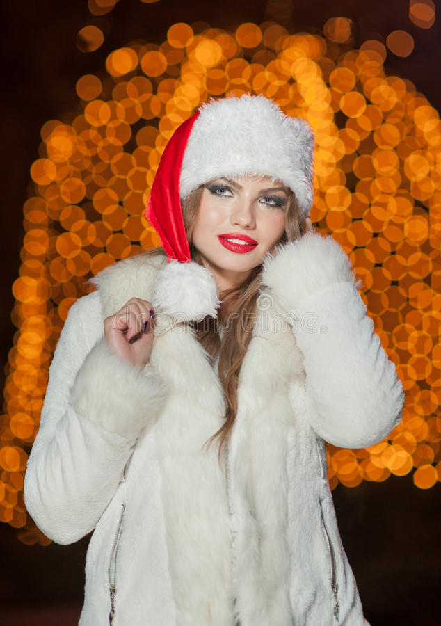 Fashionable lady wearing Xmas hat and white fur coat outdoor. Portrait of young beautiful woman in winter style. Bright picture. Of beautiful blonde woman with stock photo