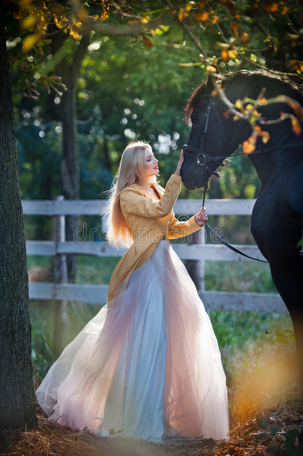 Fashionable lady with white bridal dress near black horse in forest. Beautiful young blonde woman in a long dress posing with a friendly horse. Attractive royalty free stock photo