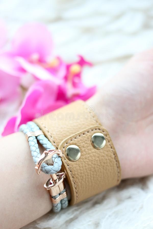 Leather bracelet for female fashion acessories. Fashionable leather bracelets on a girls wrist. Modern bracelet jewelry design. Young women fashion accessories stock images