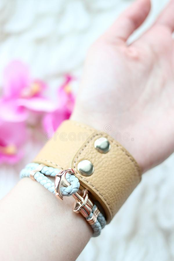 Leather bracelet for female fashion acessories. Fashionable leather bracelets on a girls wrist. Modern bracelet jewelry design. Young women fashion accessories royalty free stock photo