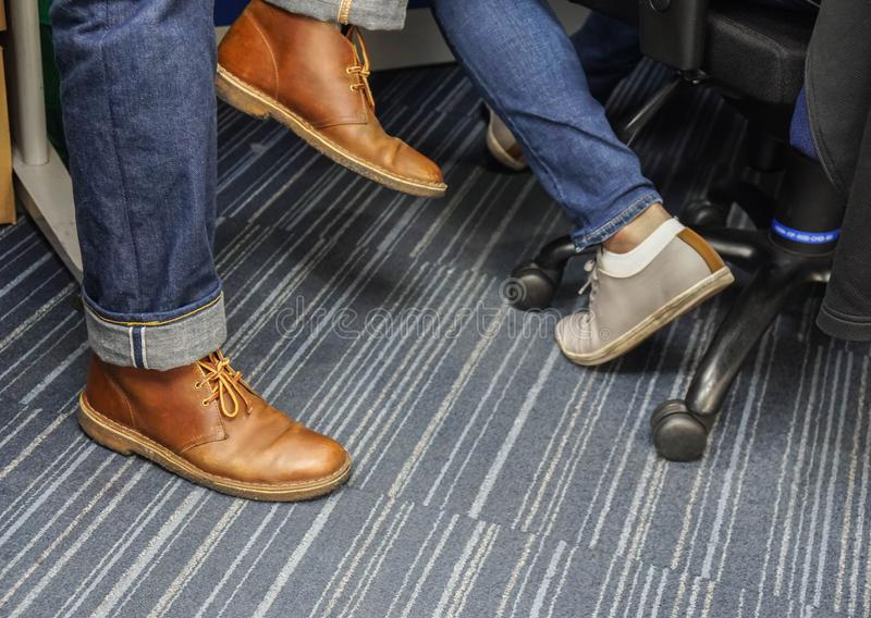 Fashionable leather men shoes with blue jeans for working in office. Close up fashionable leather men shoes with blue jeans for working in office stock image