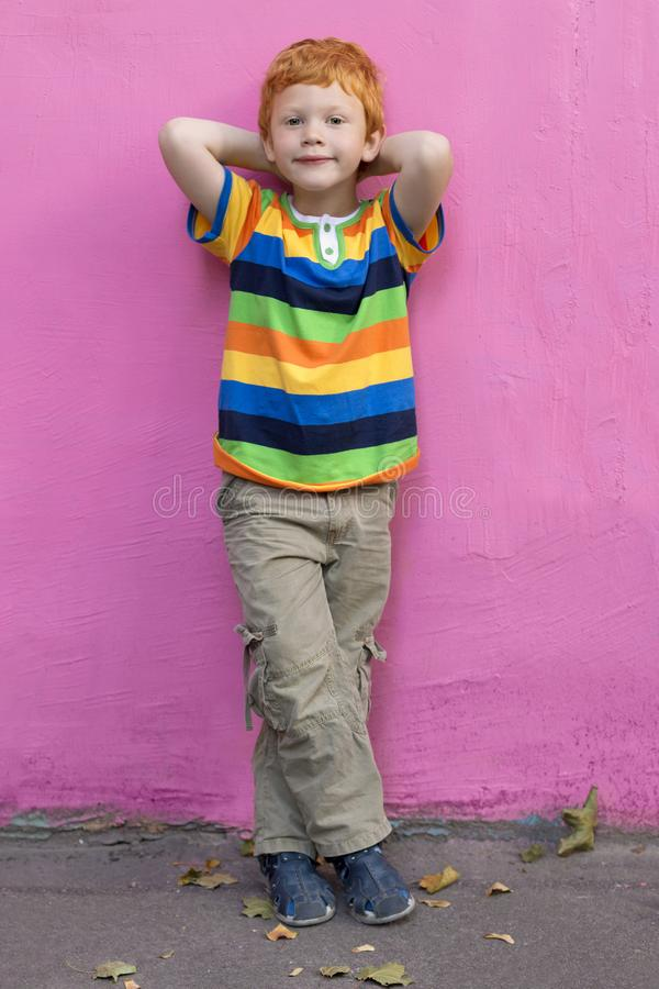 Fashionable little boy. Red-haired handsome kid model wearing trendy striped casual shirt posing against pink wall. Background enjoying good summer weather stock image