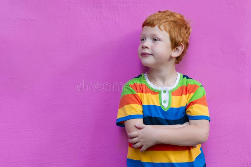 Fashionable little boy. Red-haired handsome kid model wearing trendy striped casual shirt posing against pink wall. Background enjoying good summer weather stock photo