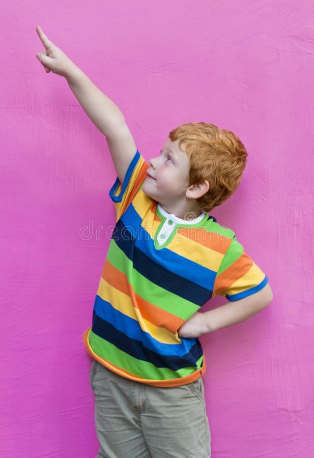 Fashionable little boy in striped t-shirt looking and pointing finger. Red-haired handsome kid model posing against pink. Wall background enjoying good summer royalty free stock image
