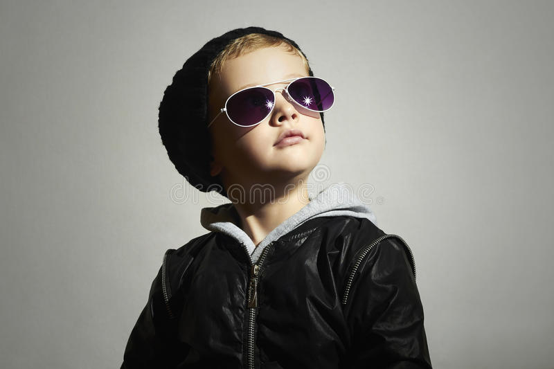 Fashionable little boy in sunglasses. Child.Posing little model in black cap stock photography