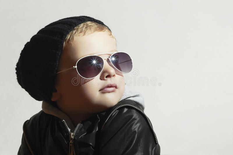 Fashionable little boy in sunglasses.Child.Winter style.Kids fashion. Little model in black cap stock image