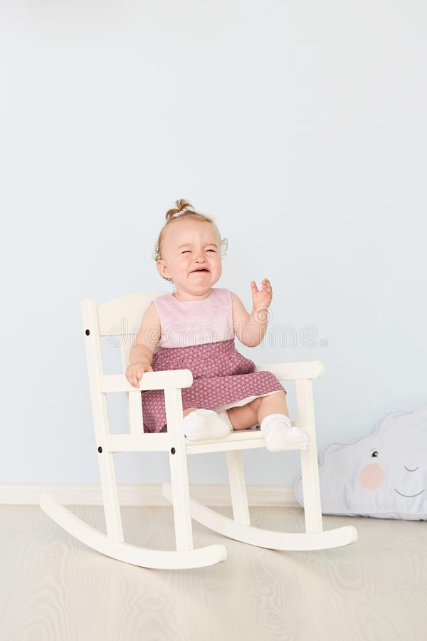 Lovely girl sits on a white chair and cries stock photography
