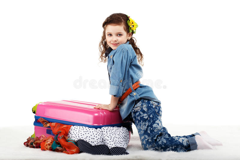 Fashionable little girl closes the suitcase with clothes. Isolated on white background royalty free stock image