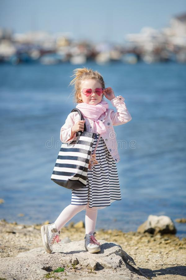 Fashionable little girl in pink sunglasses. The concept of summer vacations royalty free stock photo