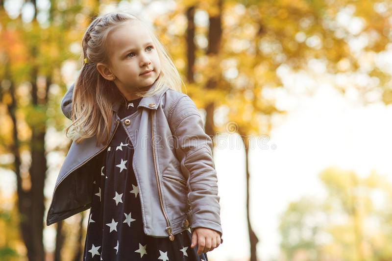 Fashionable little girl plays with autumn leaves. Happy child outdoors. Autumn kids fashion. Autumn holidays. Copy space.Beautiful stock photo