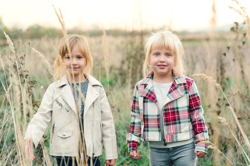 Fashionable little girls at nature. Adorable little sisters on walk at countryside. Girlfriends enjoying nature at field. Happy royalty free stock photography