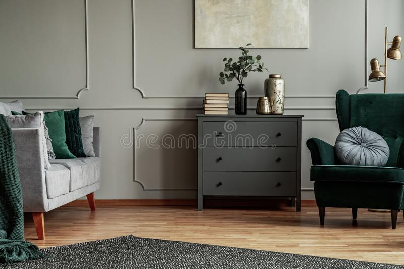Fashionable living room interior with wooden commode, scandinavian sofa and emerald green armchair stock photography
