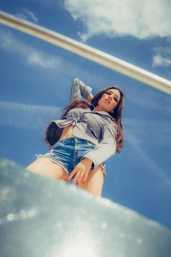 Fashionable long hair woman in jeans shorts posing on boat stock photography