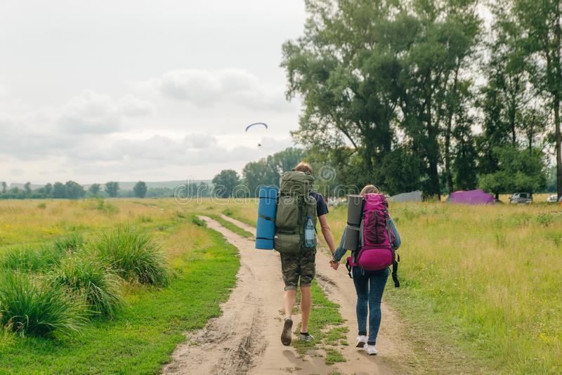 Fashionable love couple with backpacks walk. Tourist girl and man backpackers stock photos