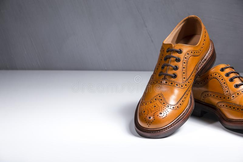 Fashionable Luxury Male Full Broggued Tan Leather Oxfords. Shoes Placed Over White Surface. Against Gray Wall. Partial View of One Shoe. Horizontal Image royalty free stock photos