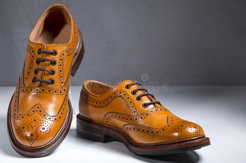 Fashionable Luxury Male Full Broggued Tan Leather Oxfords Shoes. Placed Over White Surface. Against Gray Wall Background. Horizontal Image royalty free stock images