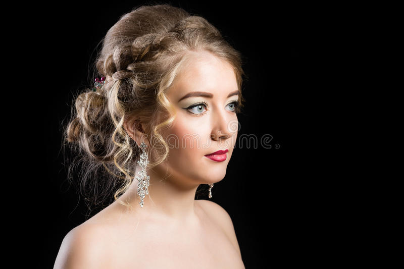Fashionable make-up for a girl with beautiful hairdress. Fashionable make-up for a young girl with a beautiful hairdress on a black background royalty free stock photo