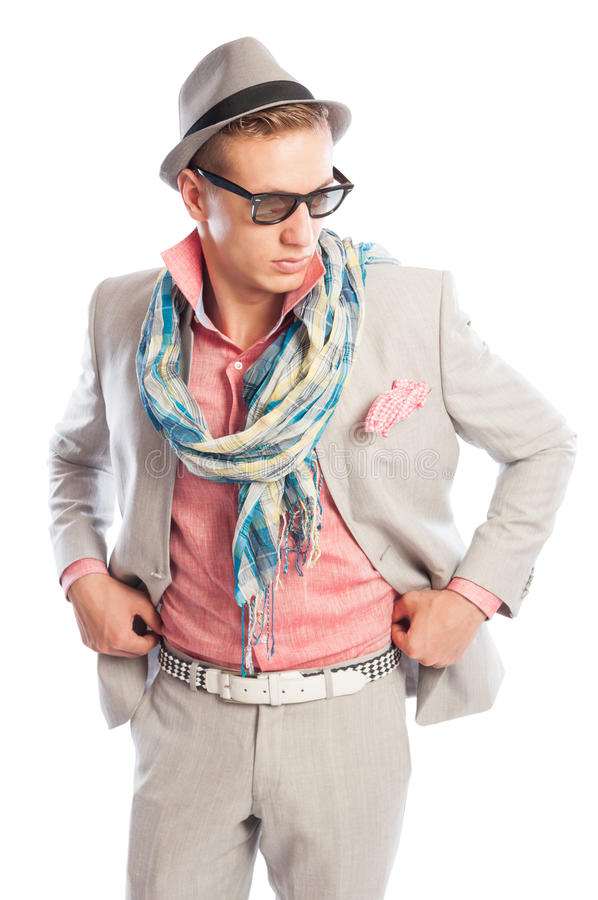Fashionable male model wearing grey suit. With , scarf, sunglasses and a hat royalty free stock image