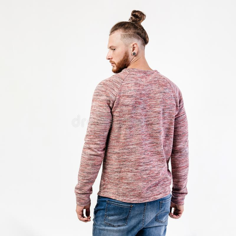 Fashionable man with beard and bun hairstyle dressed in pock-marked long sleeve sweater and jeans poses in the studio on royalty free stock photography