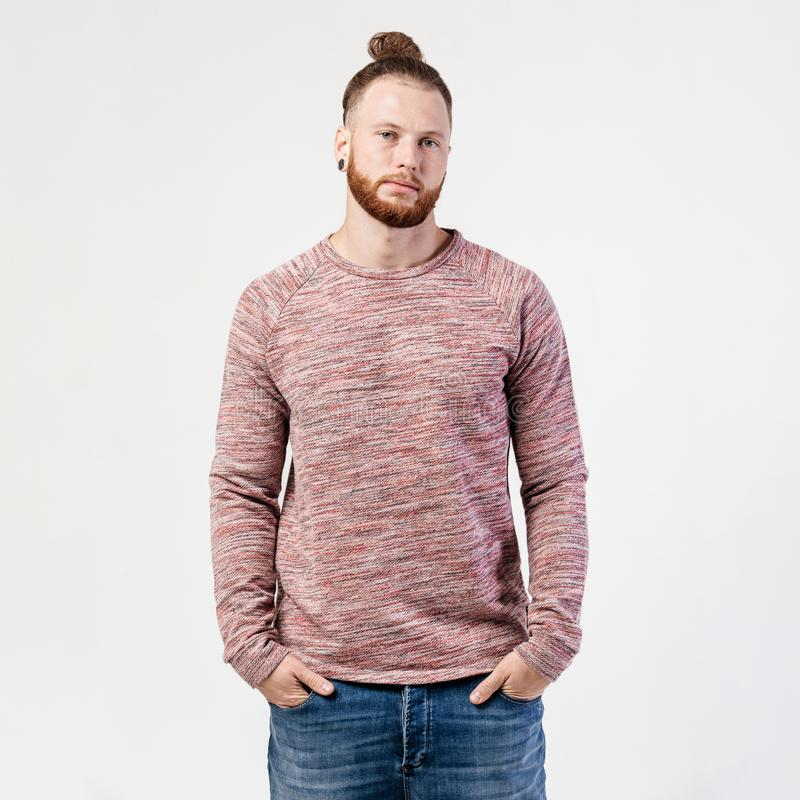 Fashionable man with beard and bun hairstyle dressed in pock-marked long sleeve sweater and jeans poses in the studio on royalty free stock images