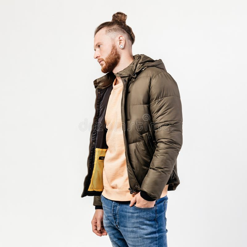 Fashionable man with beard and bun hairstyle dressed in yellow sweater, jeans and brown jacket poses in the studio on stock photography