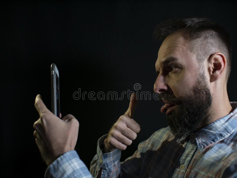 Fashionable man with a beard and mustache grimaces and takes a selfie on the phone on a black background royalty free stock photos