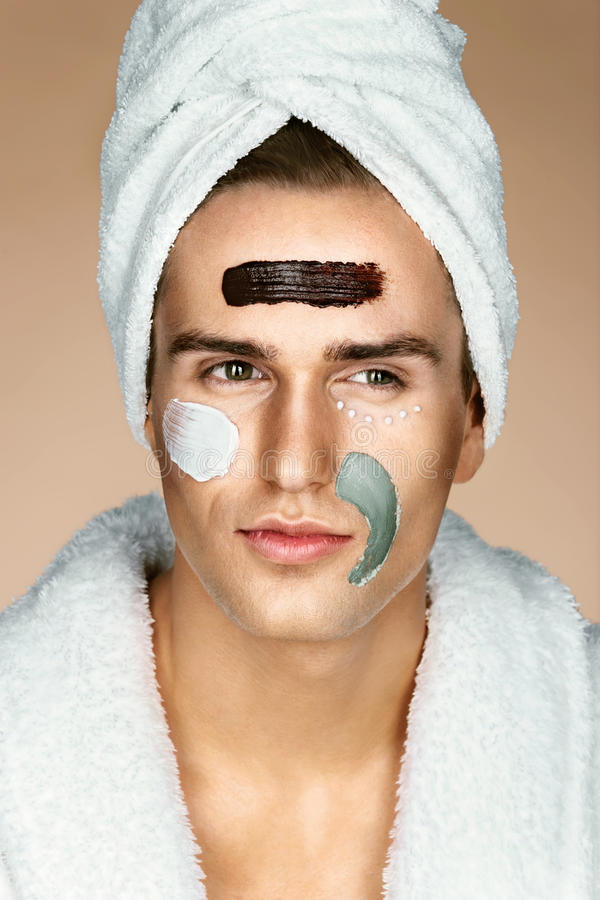 Fashionable man with three different face masks chocolate, cream and clay masks. Photo of man with perfect skin. Grooming himself stock images