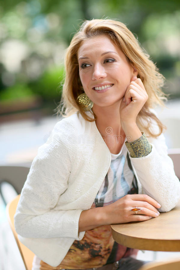 Fashionable mature woman sitting in restaurant royalty free stock image
