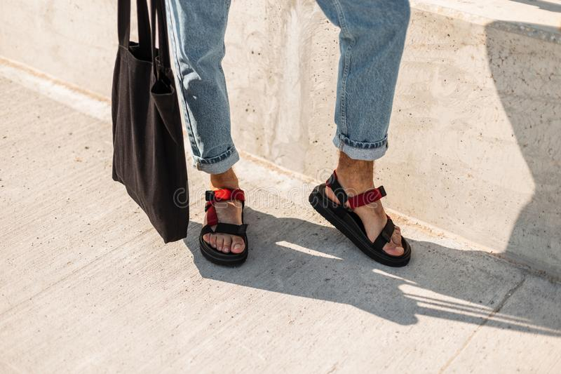 Fashionable men`s legs in vintage jeans in trendy red leather sandals with a black fabric bag stand on the pavement. Stylish new summer collection of men`s stock photos