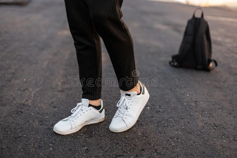 Fashionable men`s legs in white leather sneakers in trendy striped pants. Stylish men`s shoes and accessories. Casual design. Close-up of male legs royalty free stock images
