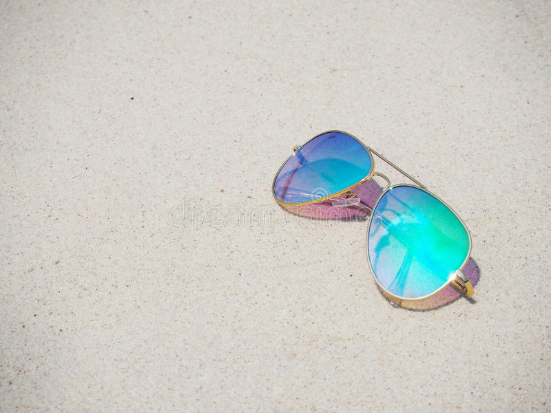 Fashionable mirror sunglasses on sand royalty free stock images
