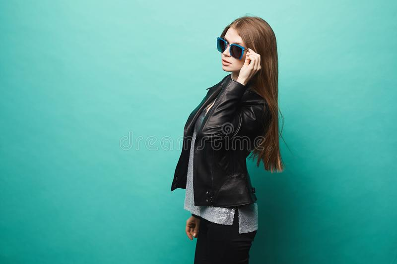 Fashionable model girl, with slim shape, in leather jacket and sunglasses, posing at green background royalty free stock photo