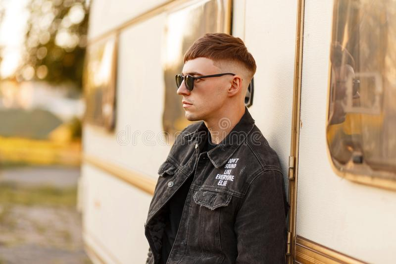 Fashionable model man with sunglasses in a black denim jacket. And a t-shirt standing near a vintage trailer stock photos