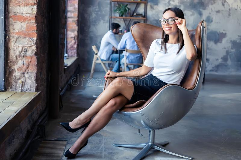 Fashionable model sitting in a chair in office. Business, elegant businesswoman. stock photography