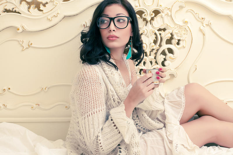 Fashionable model in trendy glasses drinking tea royalty free stock photography