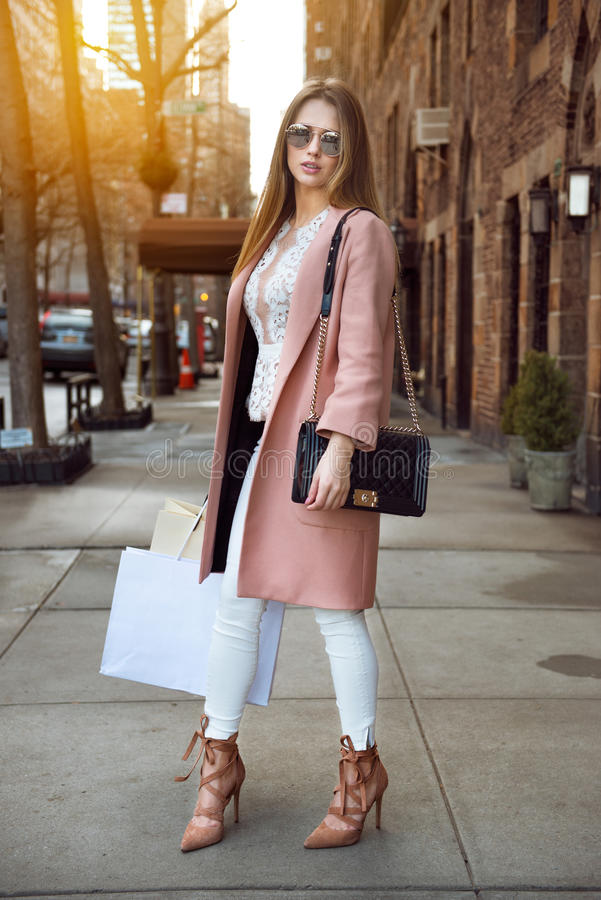 Fashionable model woman posing with shopping bags on city street stock photo