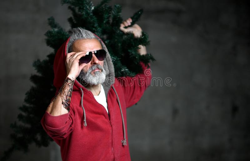 Fashionable modern millionaire Santa old man in red fashion hoodie celebrate Christmas royalty free stock image